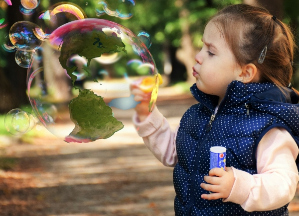 Small girl blowing bubble with map of the Americas superimposed on it