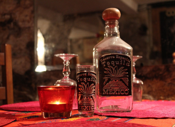 Tequila bottle shot glass and candle on table