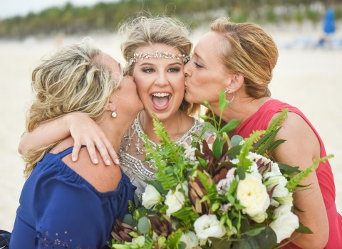 a bride getting kissed on the cheeks by her two friends