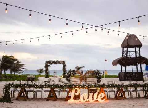 LOVE sign lit up in front of wedding set up outside