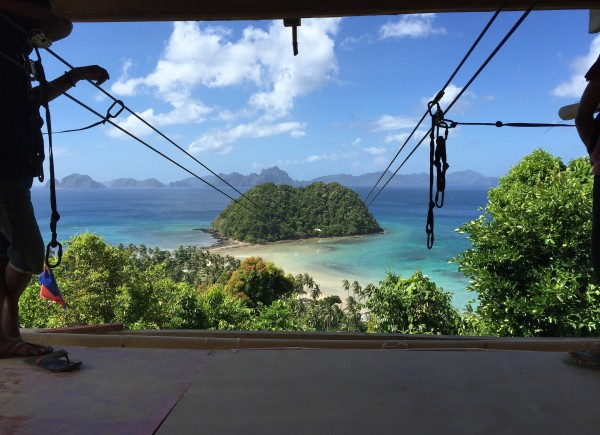 View from zipline platform onto tropical vegetation and turquoise water with small island in mid distance