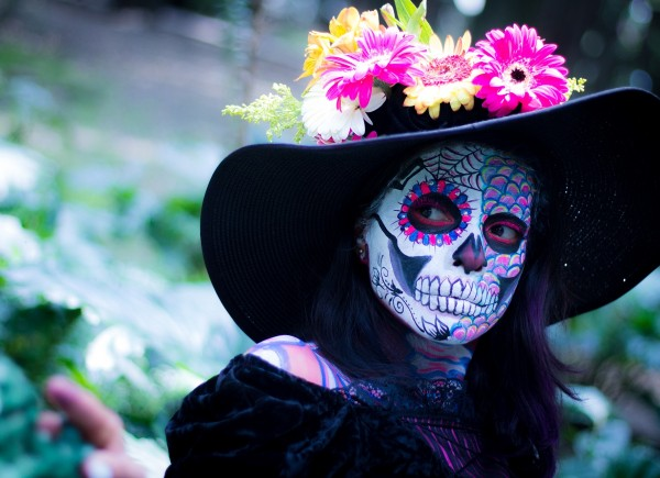 Woman with skeleton face paint and wide brimmed black hat with flowers