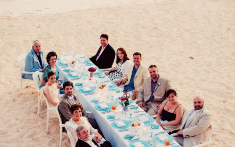 Elongated dining table set up on the beach for an event, the people sitting are dressed formally and looking at camera