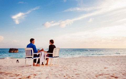 Couple in white chairs on the beach ga