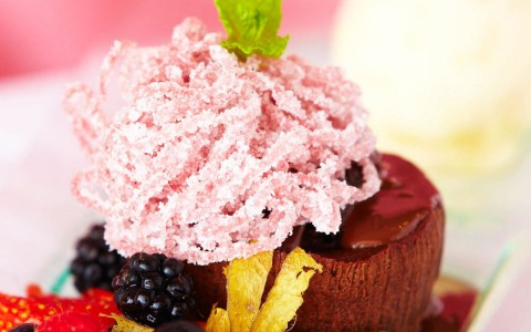 Chocolate cake dessert served on glass plate with mixed berry accompaniment and yellow flower garnish