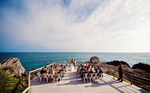 A wedding ceremony taking place on a fenced in outdoor event space that overlooks the ocean