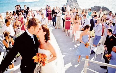 Bride and groom kissing at wedding ceremony taking place on the beach