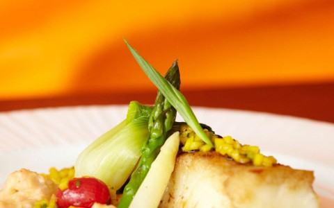 Grilled fish entree on white plate served with asparagus, risotto, and a tomato