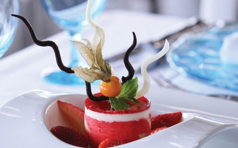 Frozen strawberry dessert with strawberry slices served on a white plate with a blue glass in the background