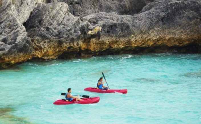 Two people kayaking on red kayaks on clear blue water near a rock cove