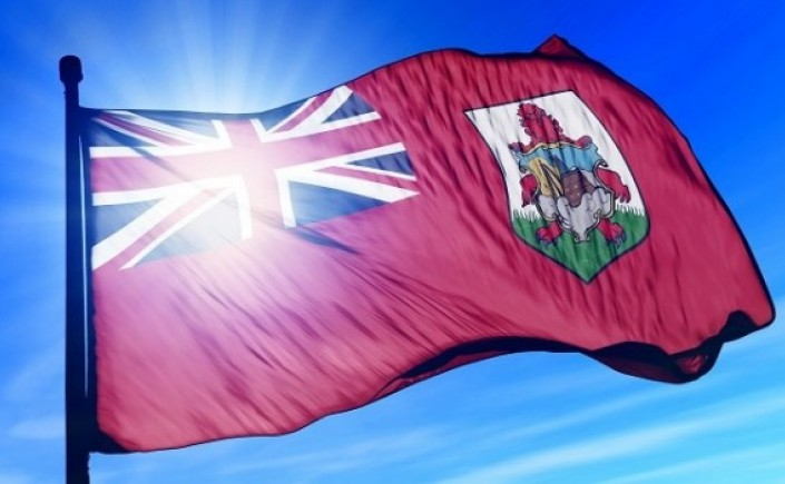 Bermuda flag blowing in the wind with the sun behind it