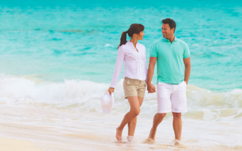 Couple holding hands gazing into each other's eyes while walking along the shoreline