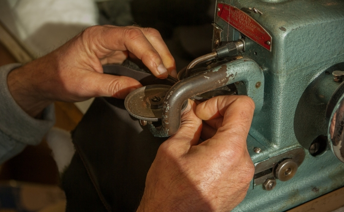 Close up on mans hands at work with sewing machine