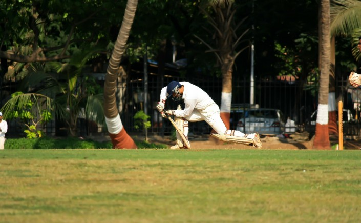 Man playing cricket swinging bat in action