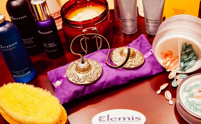 "Spa products labeled with the brand ""Elemis"" are strewn across a table, there is an assortment of bottles, creams, lotions, jars and brushes"