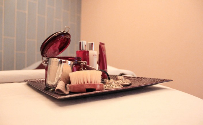 Spa treatment items displayed on a tray, they include a body brush, creams and lotions