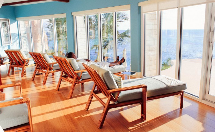 Indoor cushioned lounge chairs facing outward towards windows with ocean view, a man is lounging in one of them