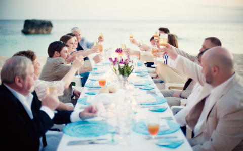 group of people eating on the beach toasting their drinks