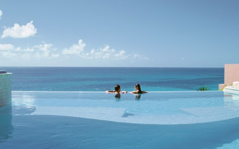 Couple overlooking edge of infinity pool with view of ocean