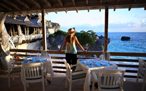 Woman wearing a straw fedora resting on balcony of casual outside dining area facing the ocean view