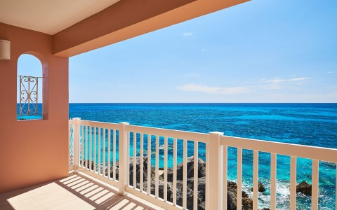 Balcony view from a suite with white railing and an ocean view