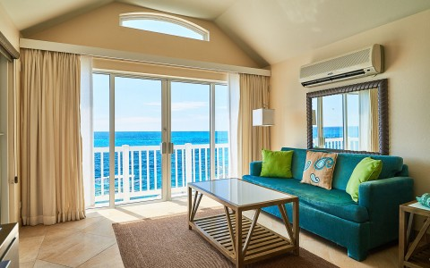 Room with an ocean view and balcony, there is a blue couch positioned under a mounted mirror on the wall and there is a glass top wooden coffee table