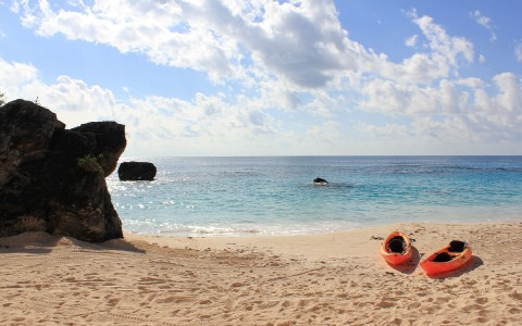 Two orange kayaks on beached on the shore of the ocean and a large boulder is o n the far left