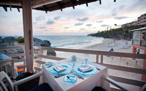 Outside dining area with a table set for two with blue plates and dining wear, the view overlooks the beach