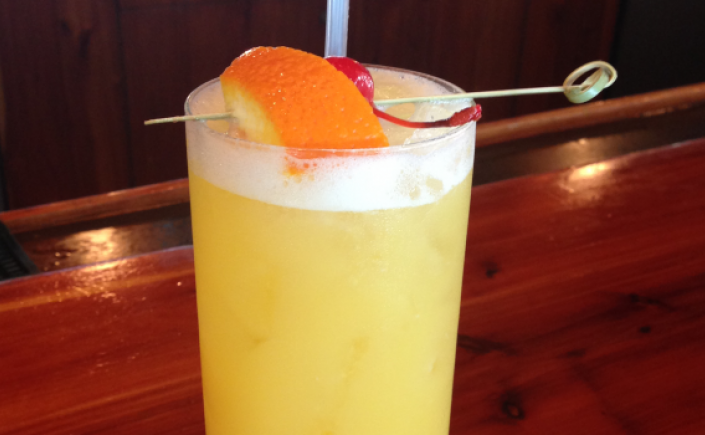 Fruity yellow mango cocktail in tall glass with orange slice