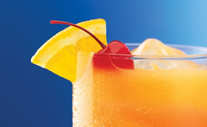 Close up of orange fruity cocktail with blue backdrop