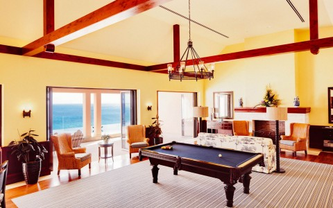Room with yellow walls and high wood beam ceilings, and a pool table centered under a lighting fixture, there is an ocean view
