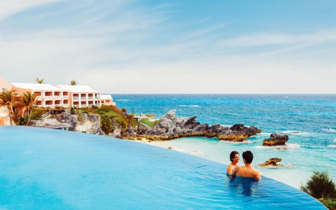 Man and woman wading near edge of infinity pool that overlooks the beach and has a resort building in the background
