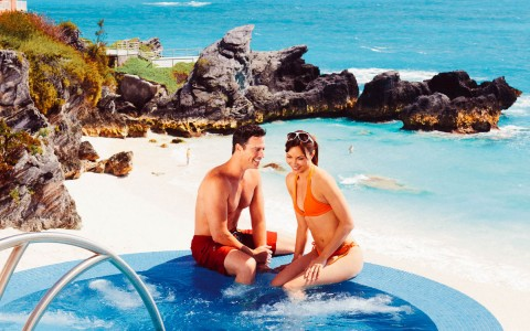 Man in red swim trunks and woman in an orange bikini enjoying a hot tub located right on the beach