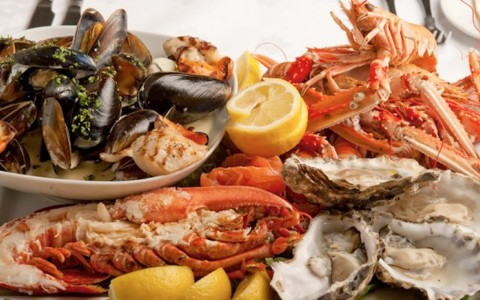 Shellfish medley: steamed mussels, half of a lobster, oysters, and crab legs with lemon wedges
