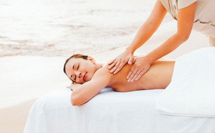 Woman receiving a back massage directly on the beach