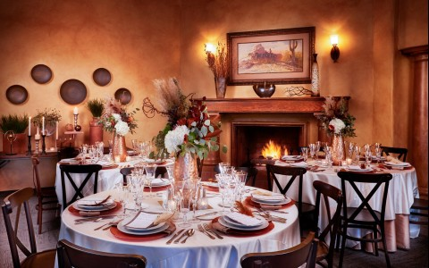 dining tables set up for an event by the fireplace