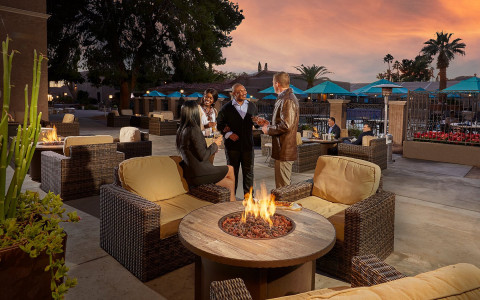 Patio with fire pit with couches surrounding as a group of adults are talking all during the sunset