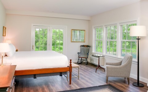 hotel room with white bed and windows