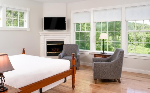 hotel room with white bed, windows and fireplace