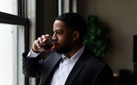 man in a suit drinking a whiskey and looking out the window
