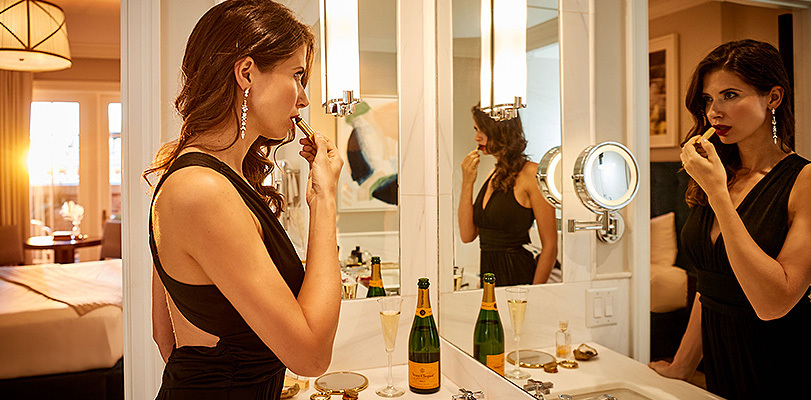 woman infront of bathroom mirror putting on lipstick