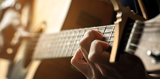 closeup of man playing guitar