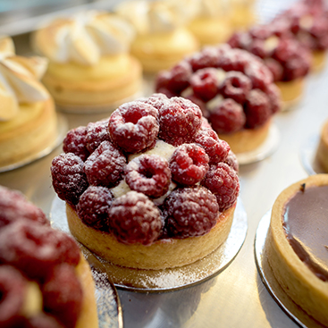 Raspberry tarts lined up in a row
