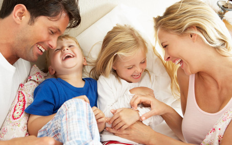 a family laughing together on a bed