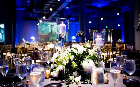 Photo credit to Bambino International, a large open art gallery with round tables set for a wedding reception