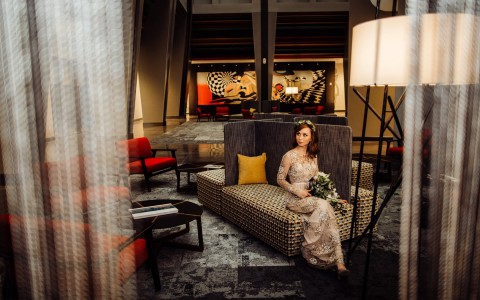 Photo credit to Olga Polo, a bride posing in a room looking out into the distance