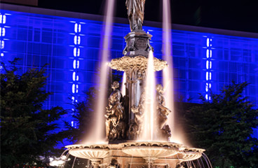 Water fountain & building with blue neon lights in the back
