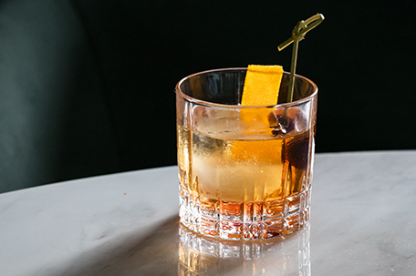 whiskey drink on the rocks with a lemon peel garnish