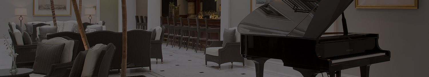 wide image of hotel lobby with black piano and seating areas