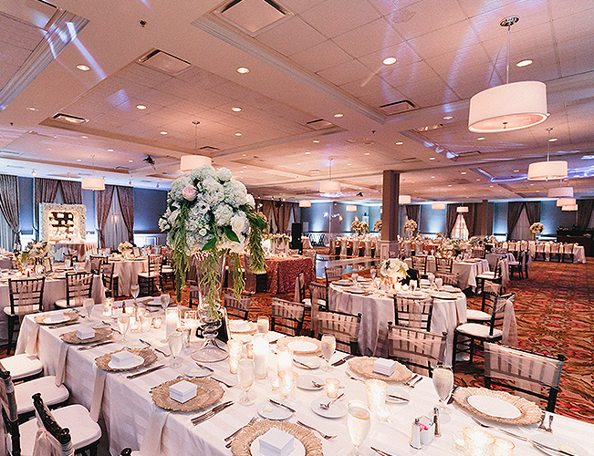 A ballroom area set up for dining with large tables draped in white tablecloths, gold decorative plates and a tall flower centerpiece in the center of a table